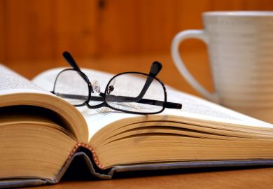 Reading glasses lying on open book