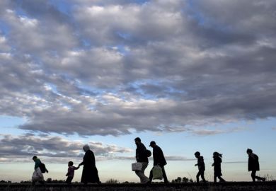 Refugees walking across a field