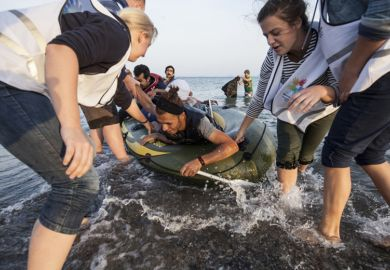 Kos, Greece - October 2015: Volunteers give a hand to migrants from Afghanistan who arrived at Kos from Turkey on a dinghy