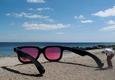 man looking through giant rose tinted sunglasses