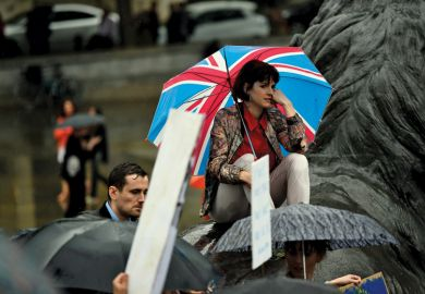 Sad woman with Union flag umbrella in rain at Trafalgar Square