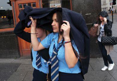 Schoolgirls shelter heads from rain, Liverpool