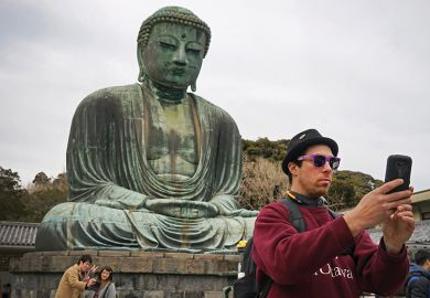 Man taking a selfie in front of a Buddha
