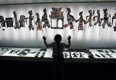 A visitor admires shadow puppets made of leather during an exhibition. China