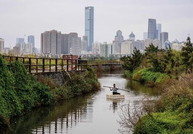 A man fishing on a polystyrene raft in Ma Tso Lung, Hong Kong, with the skyline of the Chinese mainland city of Shenzhen in the background.