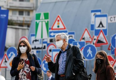 People in face masks in front of signs