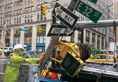 A private contractor replaces a traffic signpost with a newer version in New York City, illustrating change of direction in America