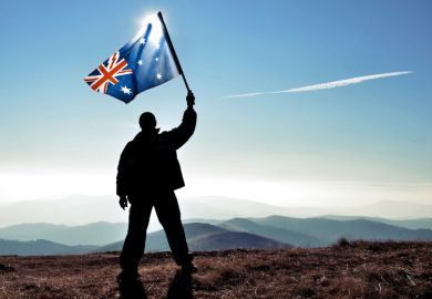 Silhouette of man waving Australian flag on hilltop