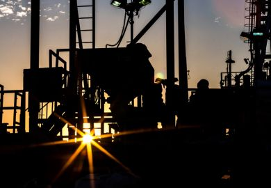 Silhouette of people working on oil rig at sunset