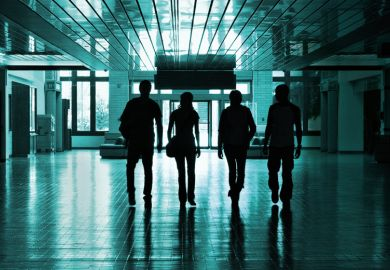 Silhouettes of students walking in university hallway