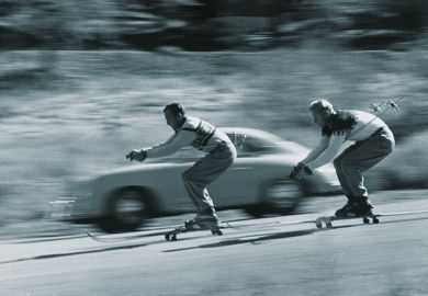 Skiers racing car down hill