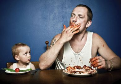 Small child and man eating at table