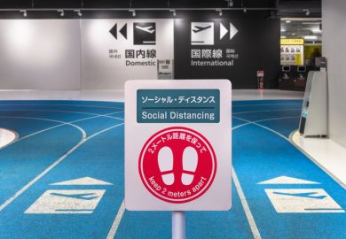 Social-distancing sign with footprints icon at Tokyo airport