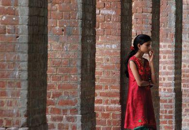 Student waiting in corridor, University of Delhi