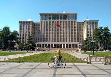 Students biking in front of the main entrance of the famous Tsinghua University building in Beijing