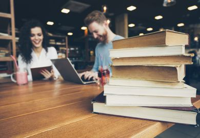 Students sitting at a table alongside a pile of books