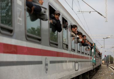 Syrian refugees leaning out of train windows