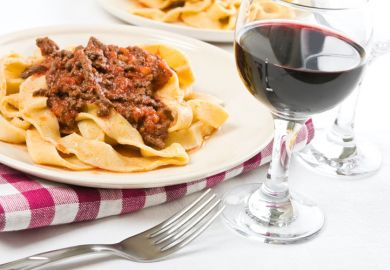 Tagliatelle with bolognese sauce and glass of red wine