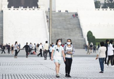 Taipei, Taiwan, March 2, 2020. Two Taiwanese girls, wearing a face mask to protect themselves from the novel coronavirus are walking in the Liberty Square, Taipei, Taiwan.