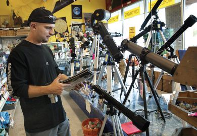 man in telescope shop