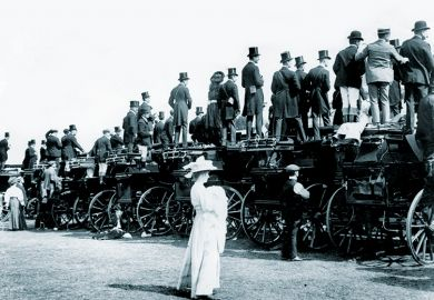 Woman standing behind men on coaches
