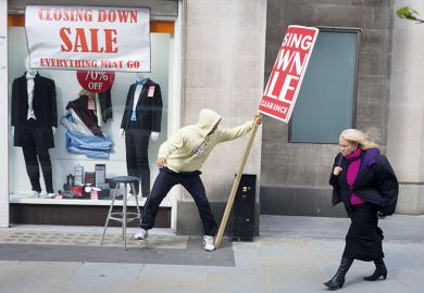 During a windy afternoon, a sandwich board man holds on to his sign advertising for a menswear shop's closure sale in central London