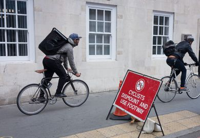 Two delivery couriers ignore a cyclist's dismount sign