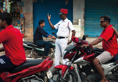 Policeman directing traffic on a street at Puducherry, India