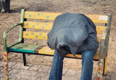 person hiding their head in their coat, sitting on a bench