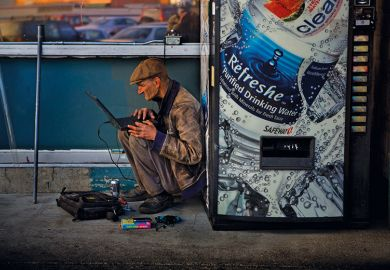 Man using computer next to vending machine
