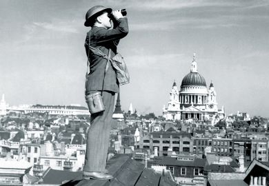 Man standing on a roof using binoculars