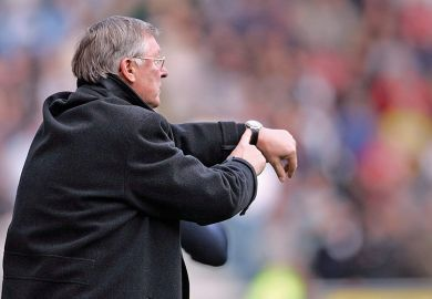 Alex Ferguson, manager of Manchester United, points to his watch