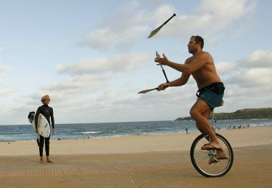 Juggler on a unicycle near surfer