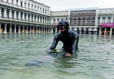 Scuba diver wading in floodwater, Saint Mark's Square, Venice