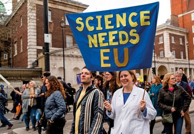 "A protester holds a ""Science needs EU"" banner on a march and rally organised by the pro-European People's Vote campaign for a second EU referendum in Parliament Square, central London on March 23, 2019"