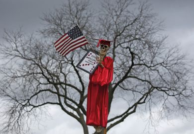 Skeleton wearing graduation gown in a tree. Northeastern Illinois University protest over funding