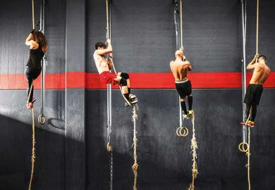 Crossfitters climbing up ropes