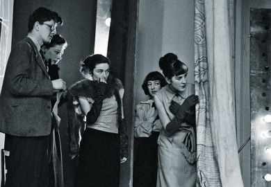 Group looking past curtains to stage