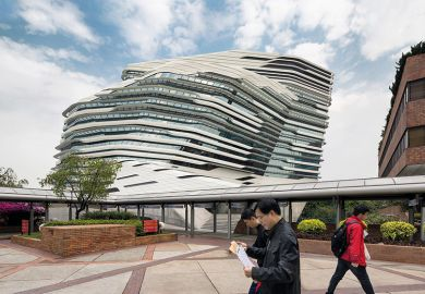 People walking past Jockey Club Innovation Tower, Hong Kong, China. Part of Hong Kong Polytechnic University