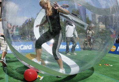woman trying to kick ball from within a zorb ball / bubble