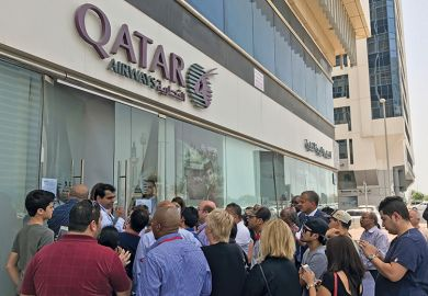 People gather outside a branch of Qatar Airways in the United Arab Emirate of Abu Dhabi on June 6 after ban on Qatari flights