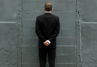 Man in front of brick wall