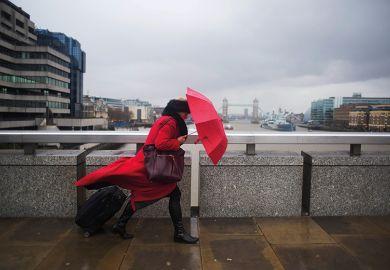 woman with umbrella walking across bridge, London