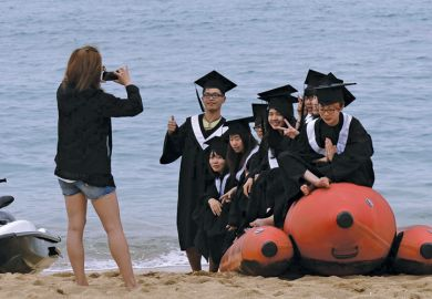 Students on inflatable boat on beach