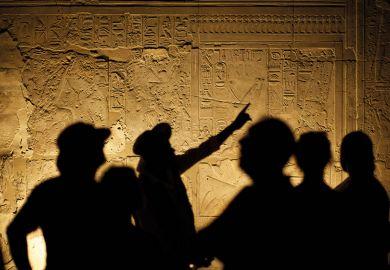 Egyptian Hieroglyphs with Tourist Archeologist Silhouettes