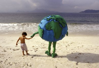 Little boy holding hands with person dressed as planet Earth