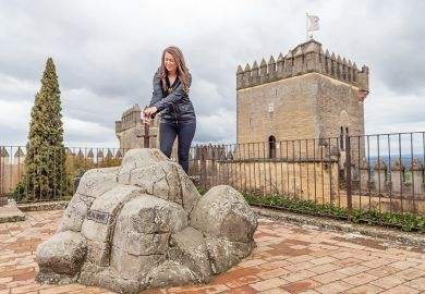 Woman pretends to pull King Arthur's sword out of its stone