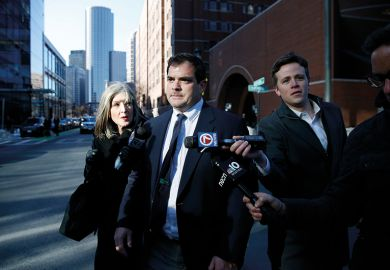 Stanford University sailing coach John Vandemoer, centre, is questioned by reporters as he leaves the John Joseph Moakley United States Courthouse in Boston on March 12, 2019.