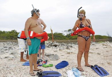 Tourists in rubber rings and flippers ready for snorkeling class