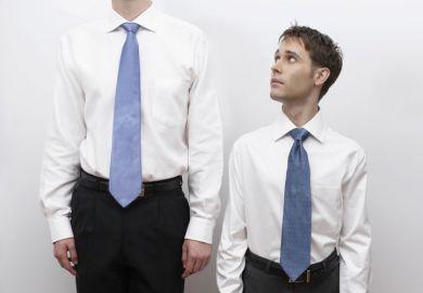 Short business man standing next to tall man